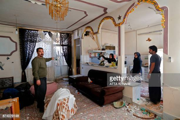 Iranians go through an apartment as they collect items from a damaged building in the town of Sarpole Zahab in the western Kermanshah province near...