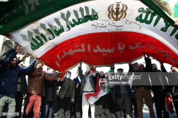 Iranians hold an Iranian flag during a protest after performing the Friday Prayer at Imam Khomeini Mosque following US' statement about backing the...