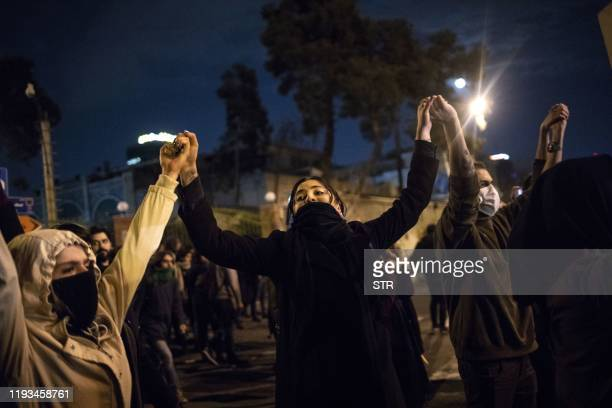 Iranians hold hands during a demonstration in front of Tehran's Amir Kabir University on January 11 2020 Demonstrations broke out for a second night...