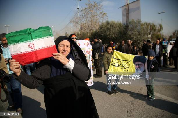 Iranians hold placards and Iranian flags during a protest after performing the Friday Prayer at Imam Khomeini Mosque following US' statement about...