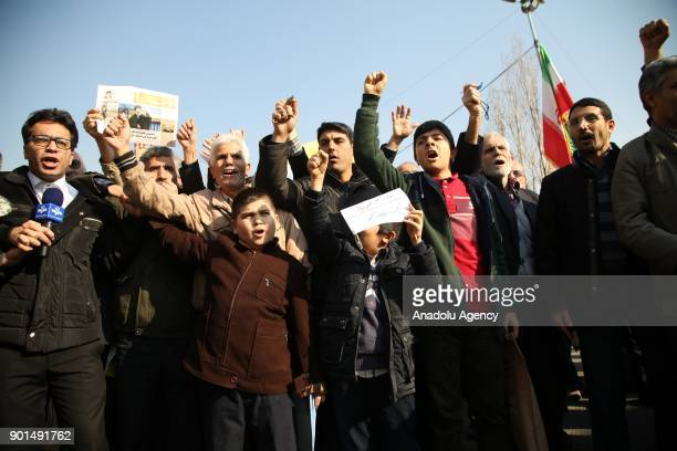 Iranians hold placards as they shout slogans during a protest after performing the Friday Prayer at Imam Khomeini Mosque following US' statement...
