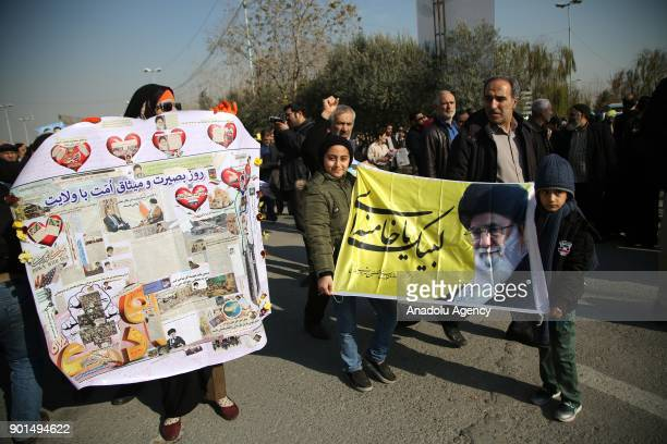 Iranians hold placards during a protest after performing the Friday Prayer at Imam Khomeini Mosque following US' statement about backing the...