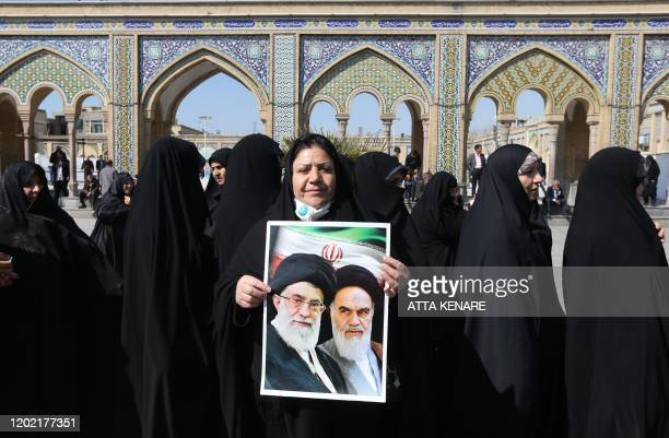 TOPSHOT Iranians hold portraits of former and current Supreme Leaders Ayatollah Ruhollah Khomeini and Ayatollah Ali Khamenei as they queue up to vote...