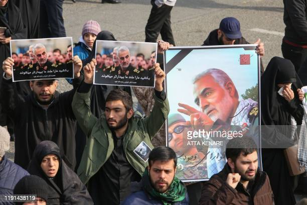Iranians hold posters of Iranian Revolutionary Guards Major General Qasem Soleimani during a demonstration in the capital Tehran on January 3 2020...