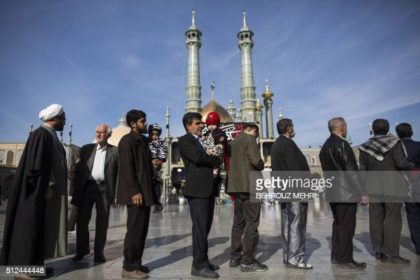 TOPSHOT Iranians hold their identification cards as they line up outside a polling station at Massoumeh shrine during the parliamentary and Assembly...