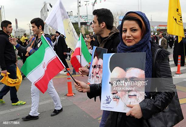 Iranians hold their national flag and posters bearing portraits of Supreme Leader Ayatollah Ali Khamenei and the founder of Iran's Islamic Republic...