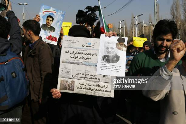 Iranians hold up a copy of Kayhan newspaper with the title New trap of the seditionists of 2009' in reference to the antigovernment protests nine...