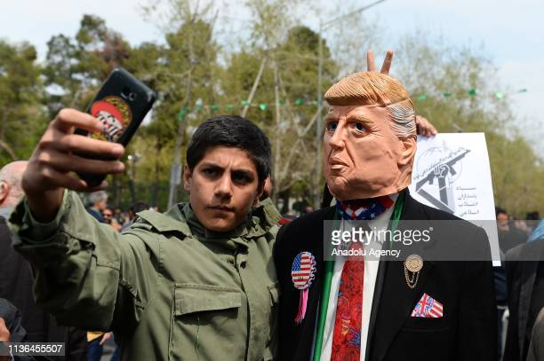 Iranians hold US President Donald Trump mask as they take part in a protest against the Trump administration's designation of Iran's Islamic...