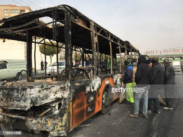 Iranians inspect the wreckage of a bus that was set ablaze by protesters during a demonstration against a rise in gasoline prices in the central city...