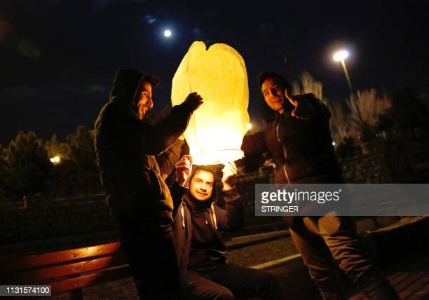 Iranians light a lantern in a park in Tehran on March 19 2018 during the Wednesday Fire feast or Chaharshanbeh Soori held annually on the last...