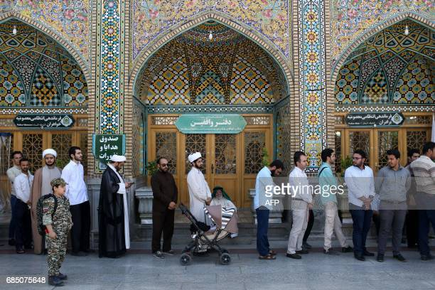Iranians line up to cast their ballots for municipal and presidential elections in the holy city of Qom 130kms south of Tehran on May 19 2017 / AFP...