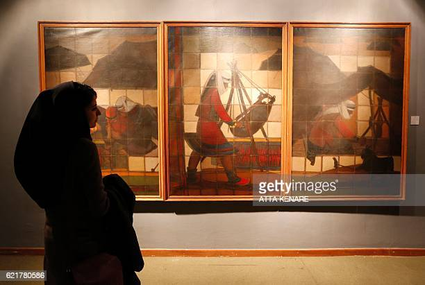 Iranians look at a painting by Iranian artist Jalil Zyapour during the opening of the Iranian and Arab modern art exhibition at Tehran's Museum of...