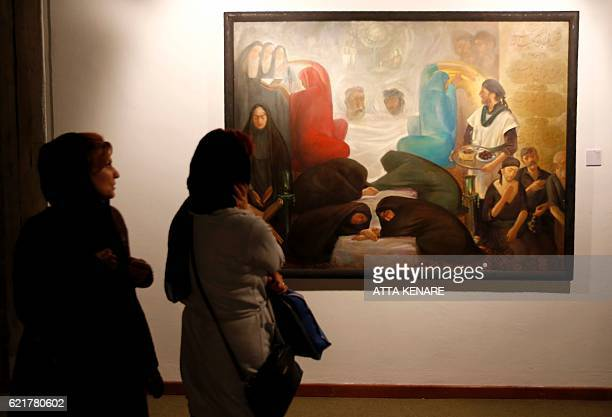 Iranians look at a painting by Iranian artist Kazem Chalipa during the opening of the Iranian and Arab modern art exhibition at Tehran's Museum of...