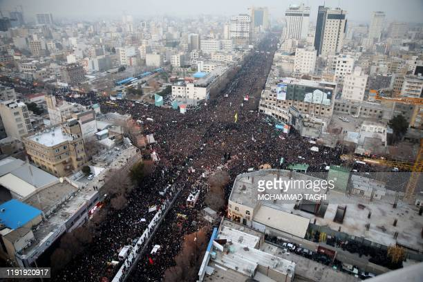 Iranians march behind a vehicle carrying the coffins of slain major general Qassem Soleimani and others as they pay homage in the northeastern city...