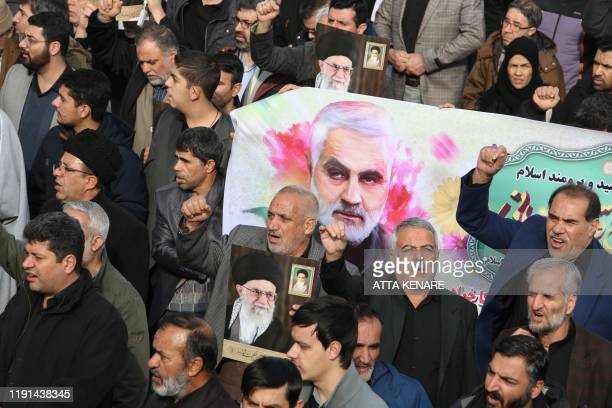 TOPSHOT Iranians march with a banner bearing an illustration of Iranian Revolutionary Guards Major General Qasem Soleimani during a demonstration in...
