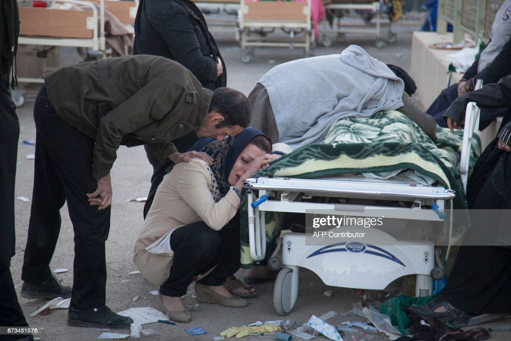TOPSHOT - Iranians mourn over the body of a victim following a 7.3-magnitude earthquake in Sarpol-e Zahab in Iran's western province of Kermanshah on November 13, 2017. / AFP PHOTO / TASNIM NEWS / Farzad MENATI