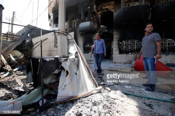 Iranians observe the headquarters of pro-Iranian Shiite militia Asa'ib Ahl al-Haq after it was burnt down by a group of demonstrators in Iraq's oil...