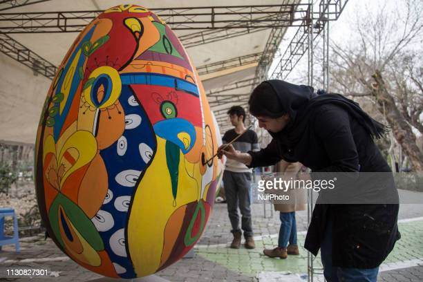 Iranians paint on giant decorative eggs at the Shahr park during an event organized by the municipality of Tehran on March 14 ahead of the Persian...
