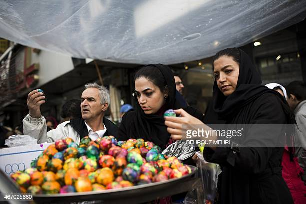 Iranians pick painted eggs to buy for Noruz festivities the Persian new year celebrations at Tajrish square market in Tehran on March 20 on the eve...