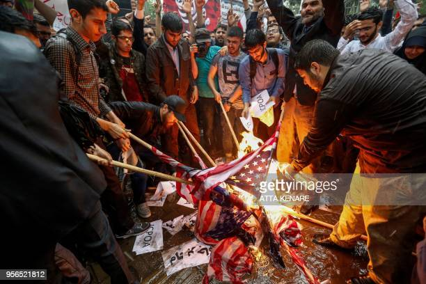 TOPSHOT Iranians pour fuel on US flags set aflame during an antiUS demonstration outside the former US embassy headquarters in the capital Tehran on...