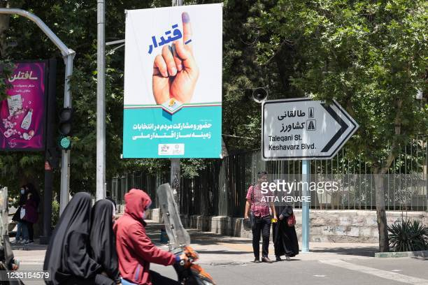 Iranians ride on a motorcycle past an electoral poster in the capital Tehran, on May 29, 2021. - Iran's presidential election campaign officially...