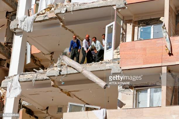 Iranians salvage a rug as they bring it down from a damaged building in the town of Sarpole Zahab in the western Kermanshah province near the border...