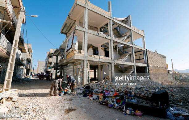 Iranians salvage their furniture and household appliances as they bring them outside the damaged buildings in the town of Sarpole Zahab in the...