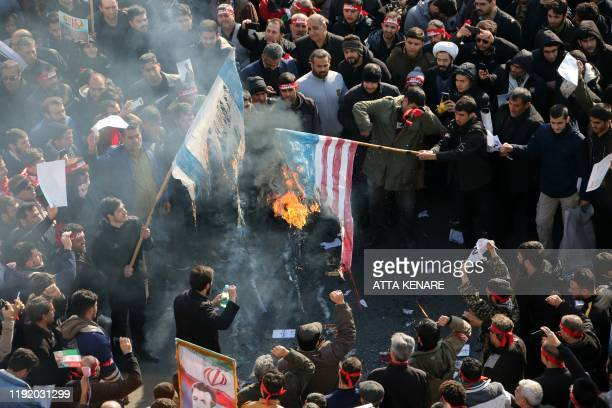 Iranians set a US and an Israeli flag on fire during a funeral procession organised to mourn the slain military commander Qasem Soleimani Iraqi...
