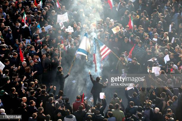 TOPSHOT Iranians set a US and an Israeli flag on fire during a funeral procession organised to mourn the slain military commander Qasem Soleimani...