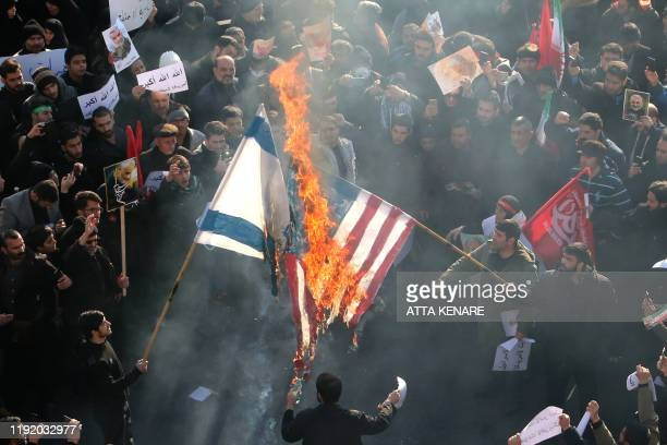 Iranians set a US and an Israeli flag on fire during a funeral procession organised to mourn the slain military commander Qasem Soleimani, Iraqi...