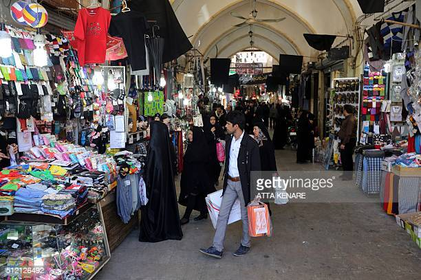 Iranians shop at the ancient Grand Bazaar of the holy city of Qom 130 kilometres south of Tehran on February 24 2016 Women make up 504 percent of...