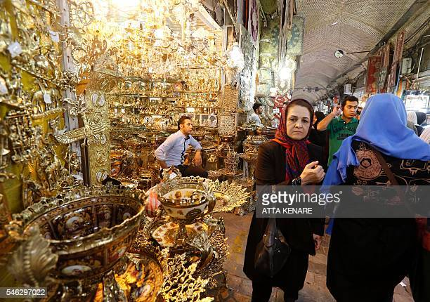 Iranians shop in Tehran's ancient Grand Bazaar on July 11 2016 A year ago a landmark nuclear deal with world powers led jubilant Iranians to dream of...