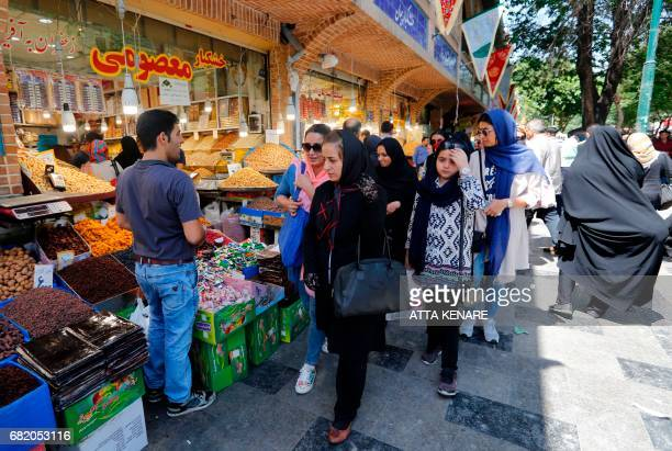 Iranians shop on a commercial street in southern Tehran's Molavi neighbourhood on May 11 2017 In a working class district of southern Tehran teeming...