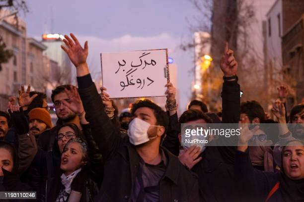 Iranians shout slogans as one of them holdsup a placard with a Persian script that reads Death To The Liar during a gathering to mark the victims of...