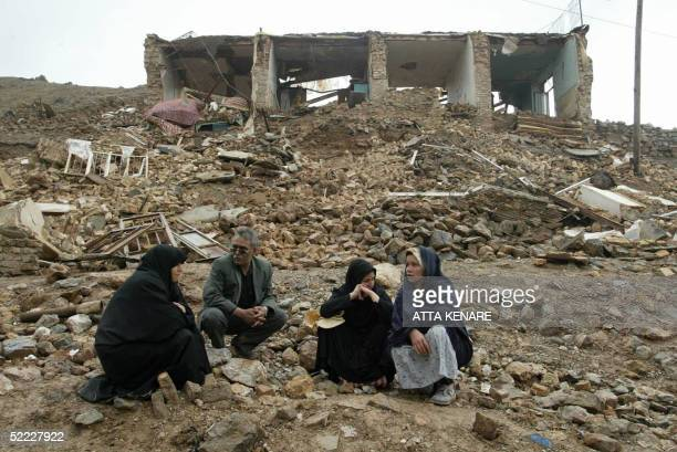 Iranians sit amid the rubble of destroyed homes in the village of Dahuyeh 22 February 2005 after an earthquake measuring 64 on the open Richter scale...
