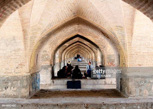 Iranians sit on the SioSe Pol bridge over the Zayandeh Rud river in Isfahan which now runs dry due to water extraction before it reaches the city on...