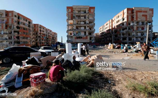 Iranians sit outside by salvaged furniture and household appliances near damaged buildings in the town of Sarpole Zahab in the western Kermanshah...