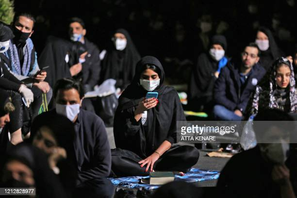 TOPSHOT Iranians some wearing face masks against the Covid19 coronavirus attend Laylat alQadr prayers one of the holiest nights during the Muslim...