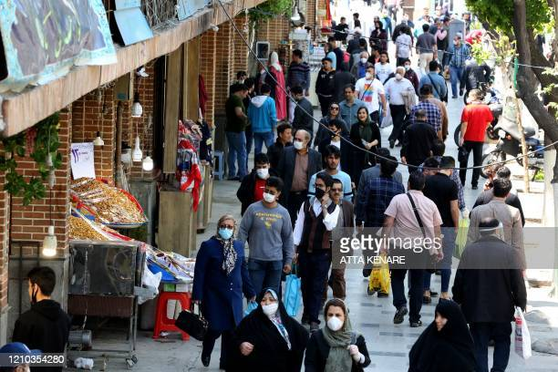 Iranians, some wearing protective gear amid the COVID-19 pandemic, shop on a street by the Grand Bazaar market in the capital Tehran, on April 18,...