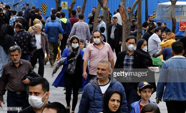 Iranians, some wearing protective masks, gather inside the capital Tehran's grand bazaar, during the Covid-19 coronavirus pandemic crises, on March...
