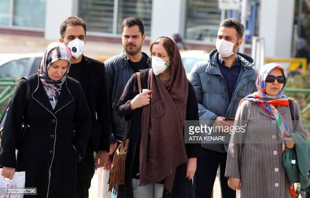 Iranians, some wearing protective masks, wait to cross a street in the capital Tehran on February 22, 2020. - Iran today reported one more death...