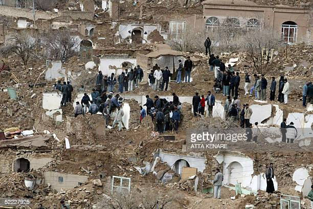 Iranians stand around the rubble of destroyed homes in the village of Dahuyeh 22 February 2005 after an earthquake measuring 64 on the open Richter...