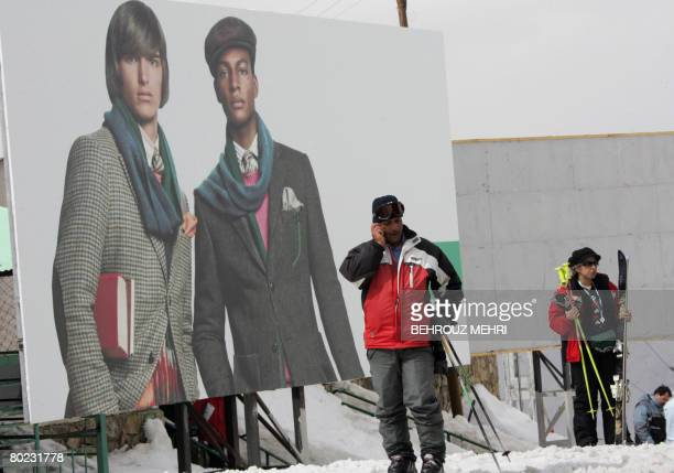 Iranians stand next to an advertisement billboard at the Dizin ski resort 120 kms northwest of Tehran on the eve of the parliamentary elections on...