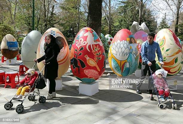 Iranians stand next to large decorative eggs displayed at the Mellat park during an event organised by the municipality of Tehran on March 18 ahead...