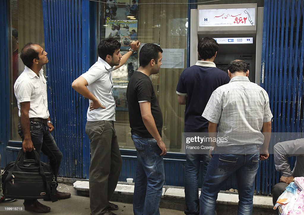 Iranians stay in a waiting line at a ATM cash machine on August 13, 2012 in Tehran, Iran.