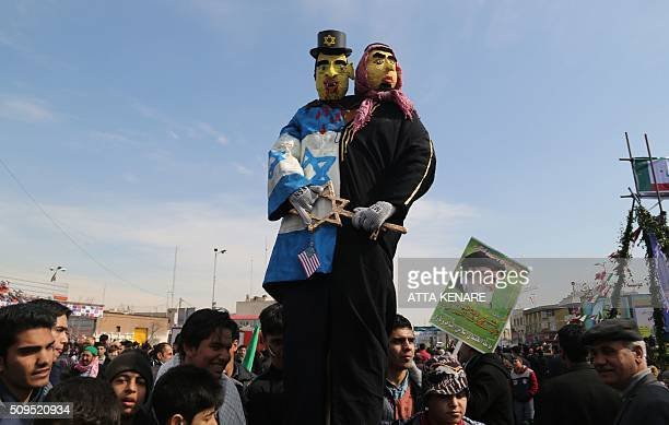 Iranians surround dummies during celebrations in Tehran's Azadi Square to mark the 37th anniversary of the Islamic revolution on February 11 2016...
