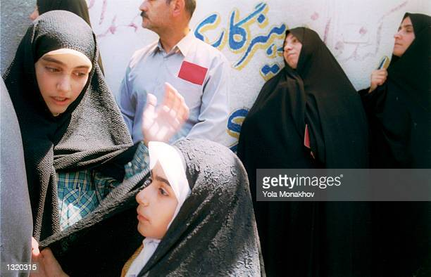 Iranians take out their passports as they queue up to vote in the presidential election June 8, 2001 in northern Tehran, Iran. President Mohammad...