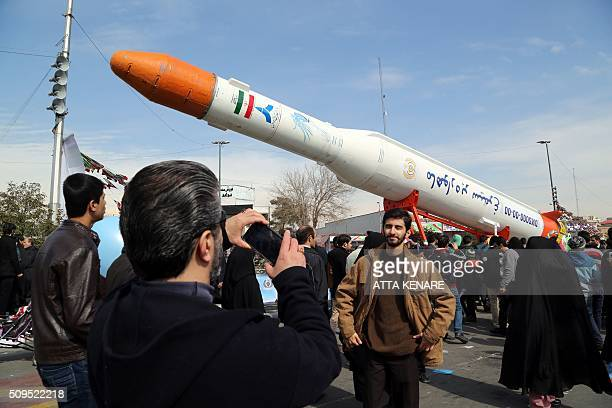 Iranians take pictures of the Simorgh satellite rocket during celebrations in Tehran to mark the 37th anniversary of the Islamic revolution on...