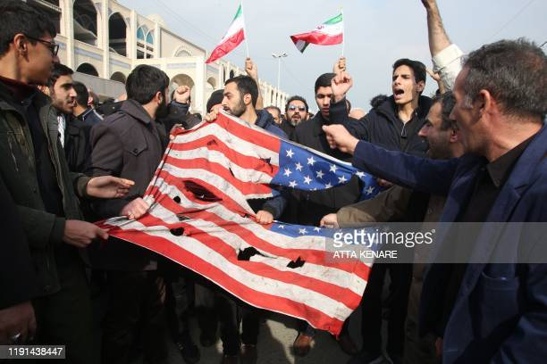 Iranians tear up a US flag during a demonstration in Tehran on January 3, 2020 following the killing of Iranian Revolutionary Guards Major General...