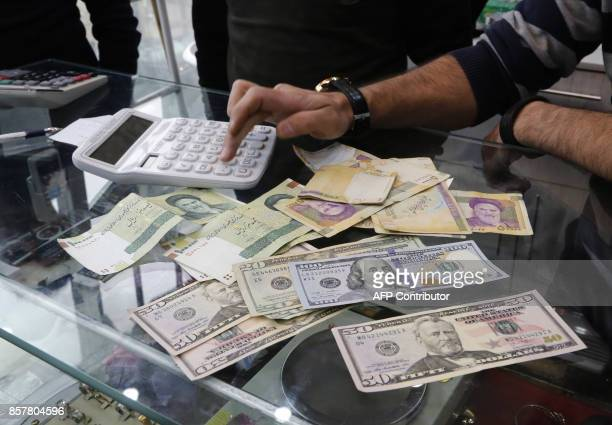 Iranians trade money at an currency exchange office in a shopping centre in Tehran on December 28 2016 / AFP PHOTO / STR